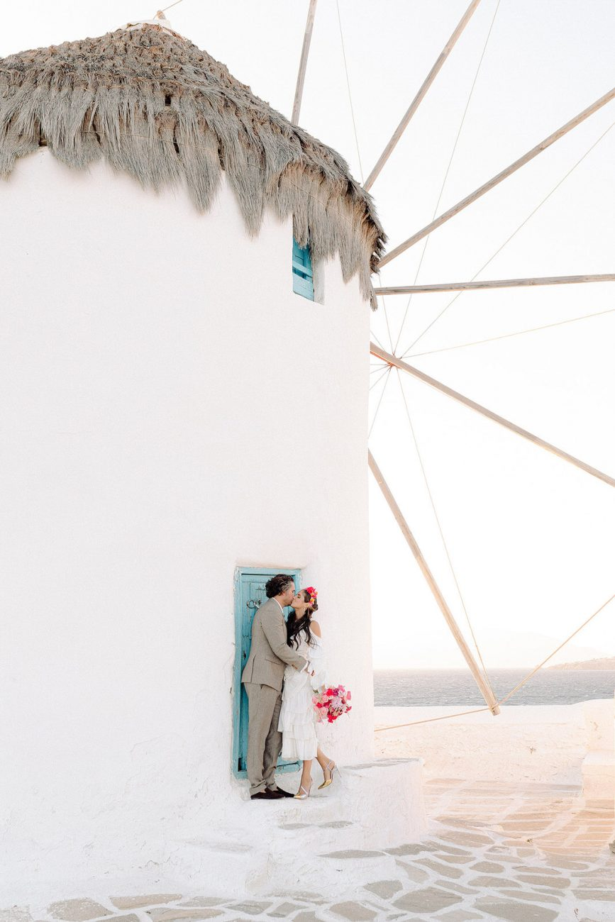couple kissing next to Mykonos windmill Mykonos wedding